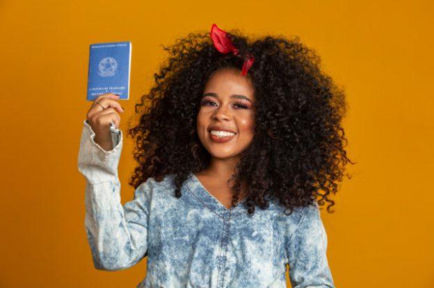 mulher segurando carteira de trabalho representando o que fazer com o primeiro salário